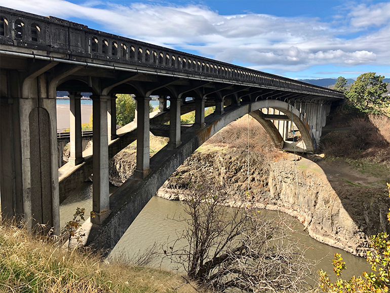 View of the Klickitat River Bridge spanning over the waterway on a partly cloudy day.